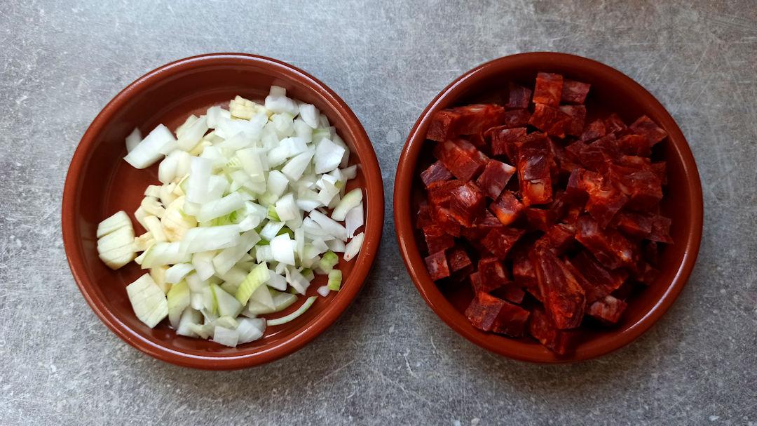 Emincer l'oignon et les gousses d'ail et couper le chorizo en cubes
